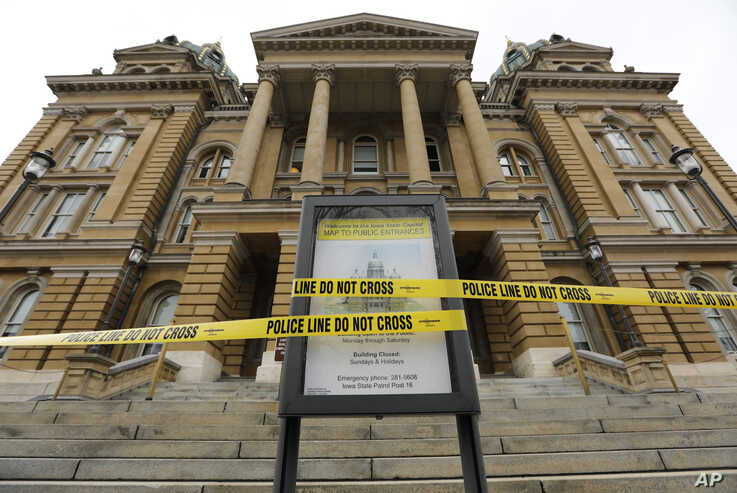 Police tape is wrapped around a sign in front of a closed entrance, Monday, March 16, 2020, at the Statehouse in Des Moines,…