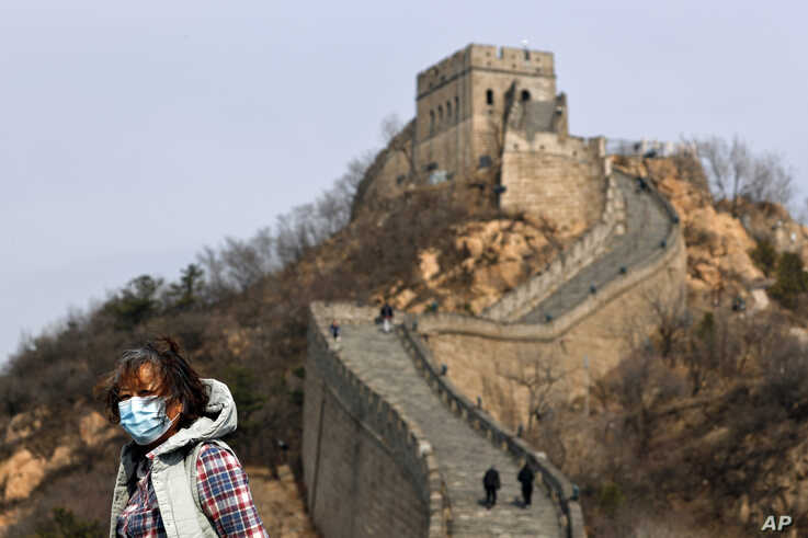 A woman wearing a protective face mask visits the Badaling Great Wall of China after it reopened for business following the new…