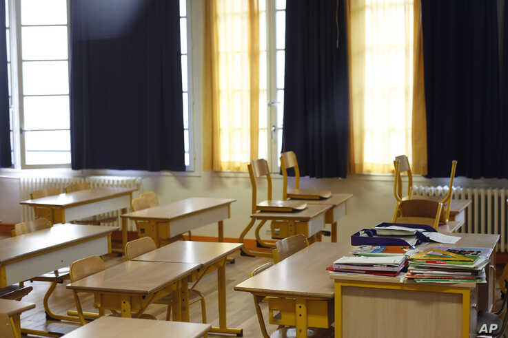 An empty classroom is seen at a closed school in Paris, Monday, March 16, 2020. France plans to close all creches, schools and…