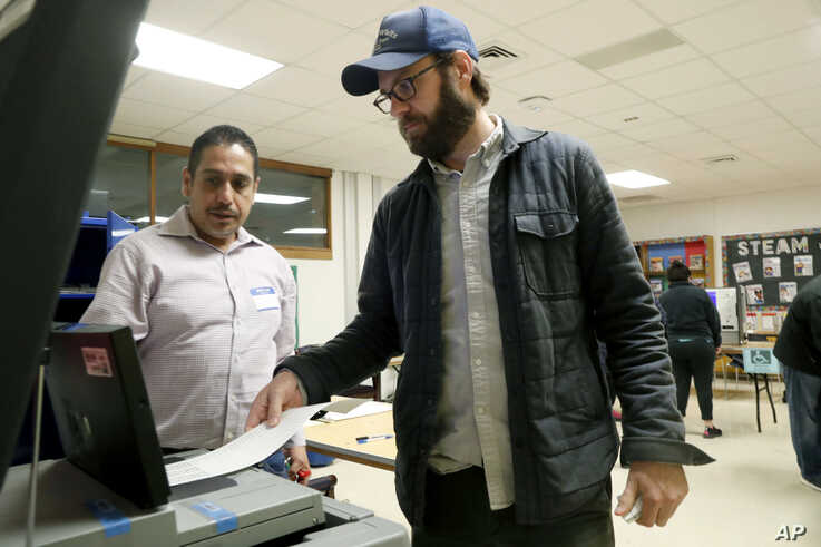 Dallas County election worker Maxx Nuñez helps Democrat Jamie Wilson cast his ballot in the Super Tuesday primary at John H…