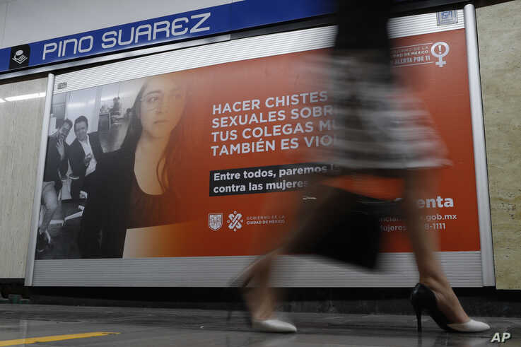 """A woman walks past a sign with a message that reads in Spanish: """"Making sexual jokes about your female colleagues is also…"""