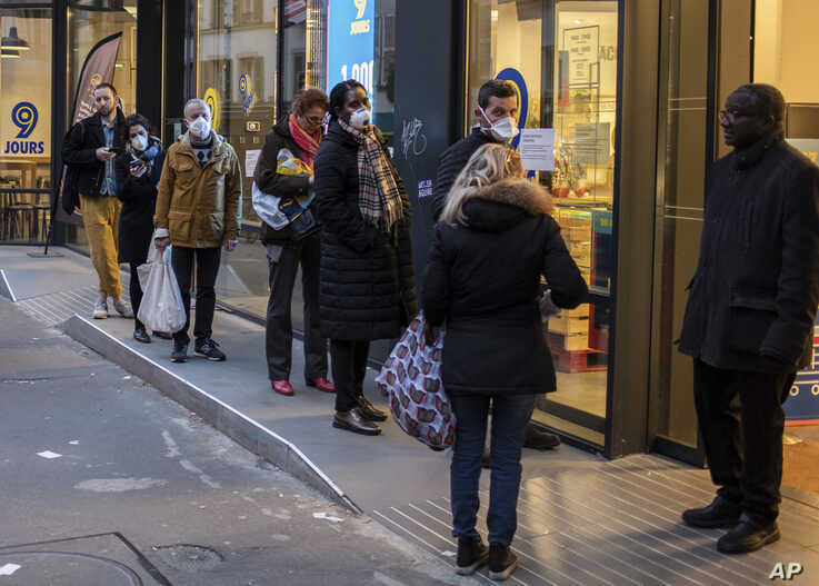 People with a protective masks line up using social distancing to queue at a supermarket in Paris, Monday, March 16, 2020…
