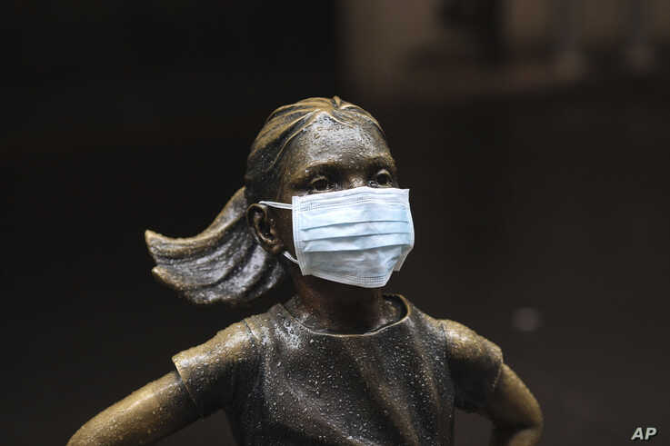 """A surgical mask is placed on The """"Fearless Girl"""" statue outside the New York Stock Exchange on Thursday, March 19, 2020, in New…"""