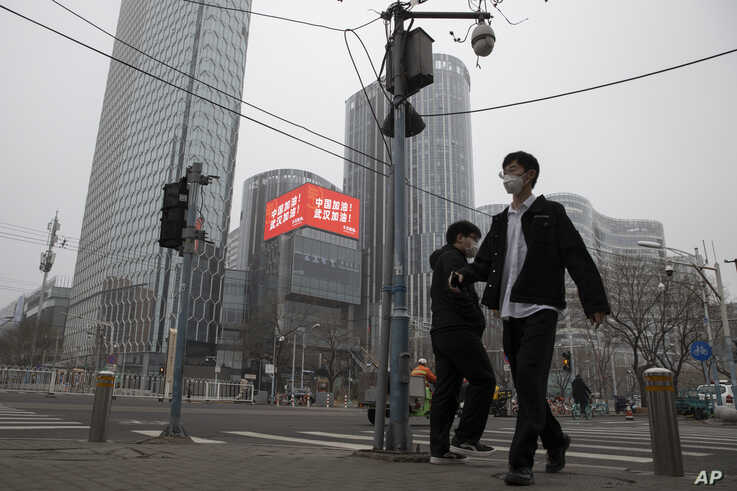"""Residents walk past a retail and office district with a screen showing propaganda which reads """"Go China! Go Wuhan"""" as…"""