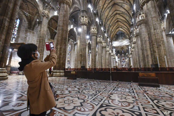 A tourist wearing a face mask takes pictures inside the Duomo gothic cathedral as it reopened to the public after being closed…