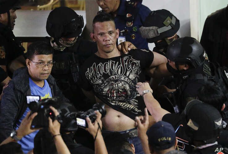 Police take hostage taker Archie Paray into custody as he speaks to media shortly after releasing all his hostages at the V…
