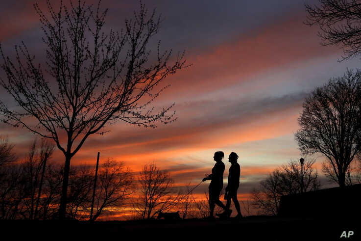 A couple walk a dog at sunset, Wednesday, March 25, 2020, in Kansas City, Mo. The city, along with neighboring counties, is…
