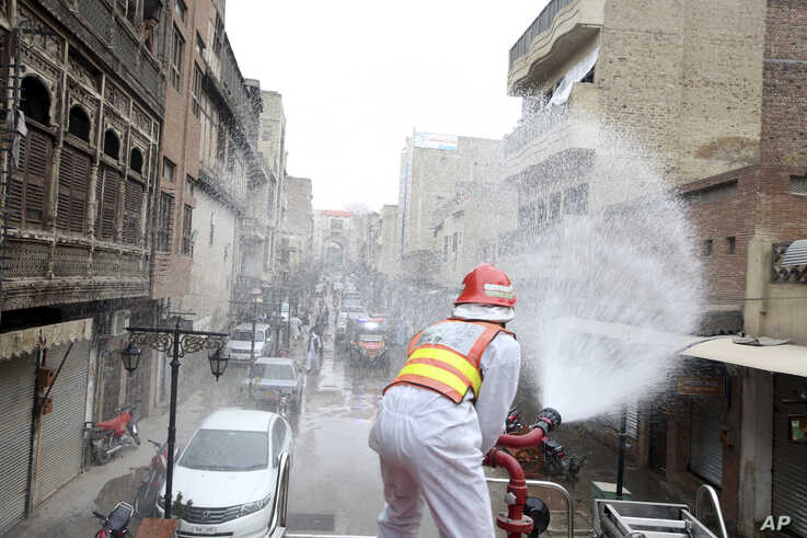 A volunteer sprays disinfectant in an effort to curb the spread of coronavirus outbreak in Peshawar, Pakistan, Monday, March 23…