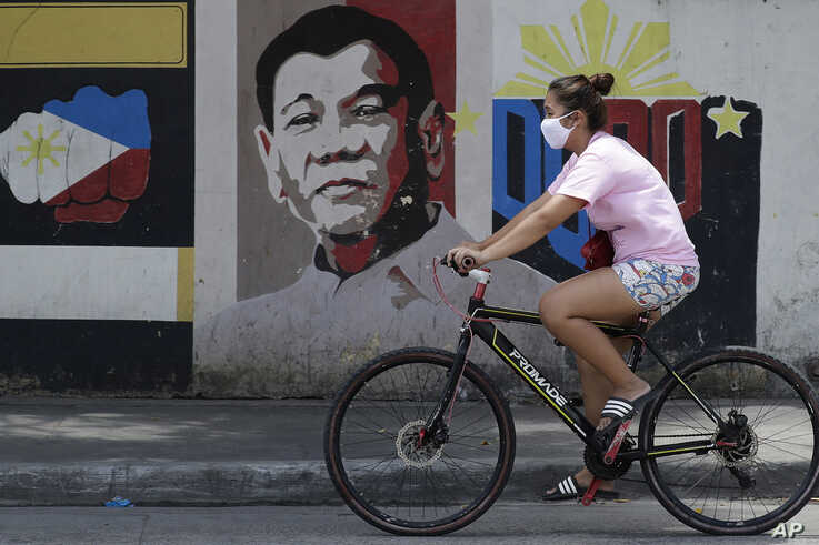 A woman wearing a protective mask rides her bicycle past an image of Philippine President Rodrigo Duterte in Manila,…