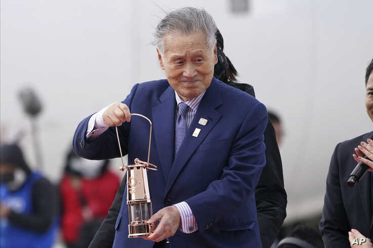 Tokyo 2020 Olympics chief Yoshiro Mori carries the Olympic flame during the Flame Arrival Ceremony at Japan Air Self-Defense…
