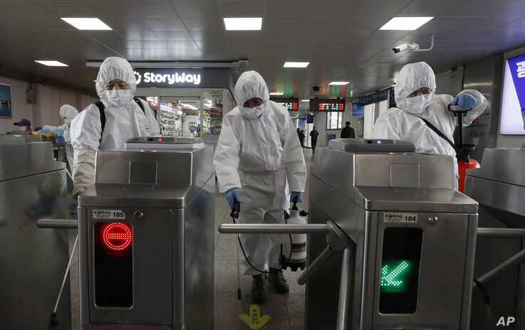 Workers wearing protective gears disinfect as a precaution against the new coronavirus at the subway station in Seoul, South…
