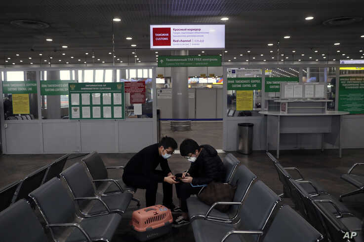 Passengers play their smart phones as they wait at an empty hall inside Sheremetyevo international airport outside Moscow,…