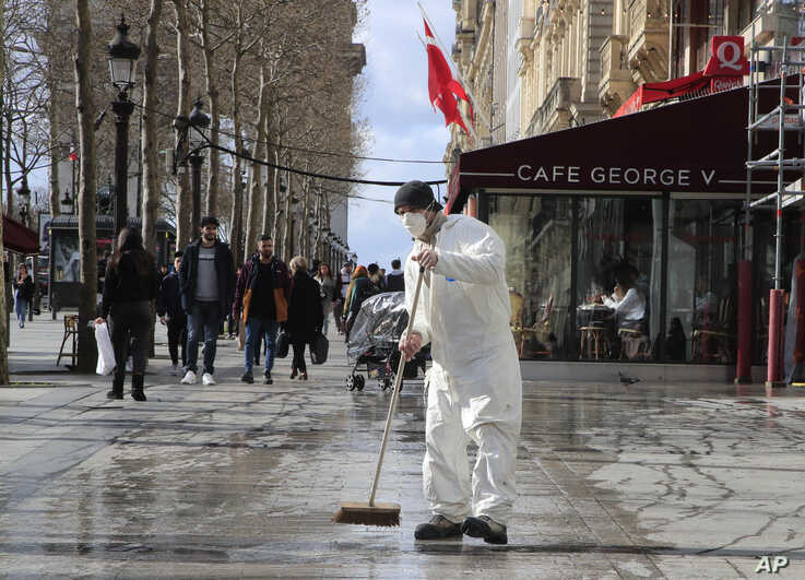 A masked worker wipes the pavement of the Champs Elysees avenue in Paris, Friday, March 13, 2020. For most people, the new…