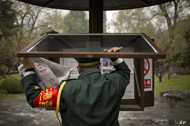 A worker changes copies of the People's Daily newspaper in a public reading display at a park in Beijing, Friday, Nov. 20, 2015…