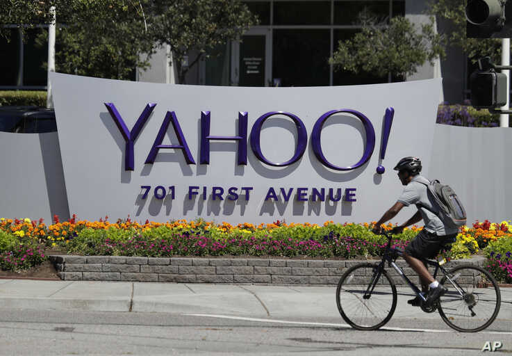 FILE - In this Tuesday, July 19, 2016 file photo, a cyclist rides past a Yahoo sign at the company's headquarters in Sunnyvale,…