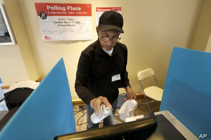 John Davis, a polling judge volunteer, sanitizes an electronic voting machine screen amid concerns about the COVID-19…
