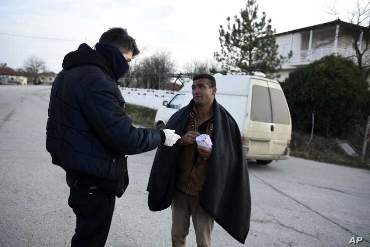 Greek authorities detain a migrant from Iran after he entered Greece from Turkey, in the village of Thourio, Evros region near…