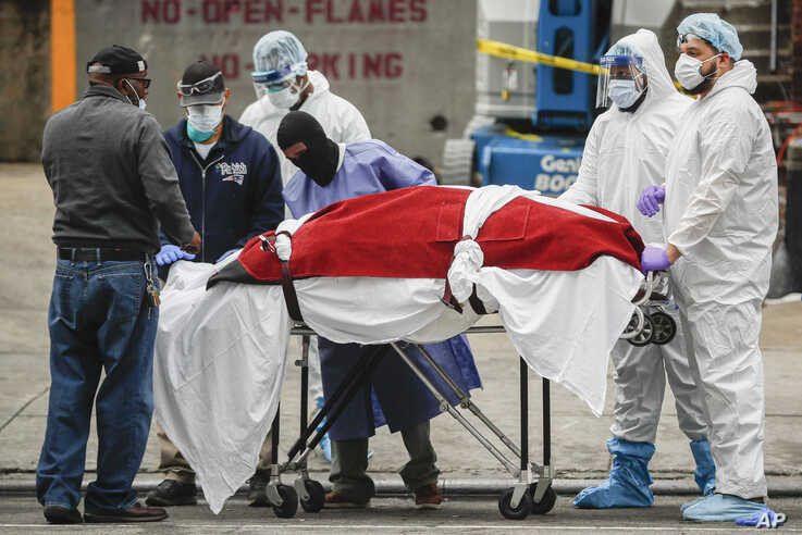 A body wrapped in plastic that was unloaded from a refrigerated truck is handled by medical workers wearing personal protective…