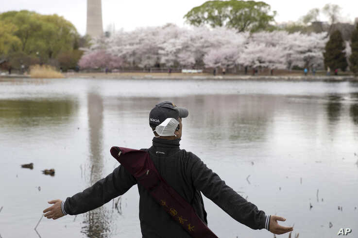A man removes his mask to stretch and take a deep breath across from cherry blossoms at the Yuyuantan Park in Beijing on…