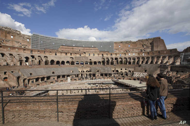 Tourists visit the Colosseum, in Rome, Saturday, March 7, 2020. With the coronavirus emergency deepening in Europe, Italy, a…