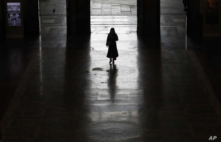 A lonely passenger leaves Milan main train station, Italy, Monday, March 9, 2020. Italy took a page from China's playbook…
