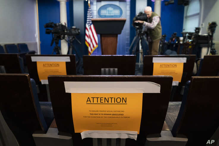 Signs in the briefing room of the White House indicate social distancing measures being taken to separate reporters working at…