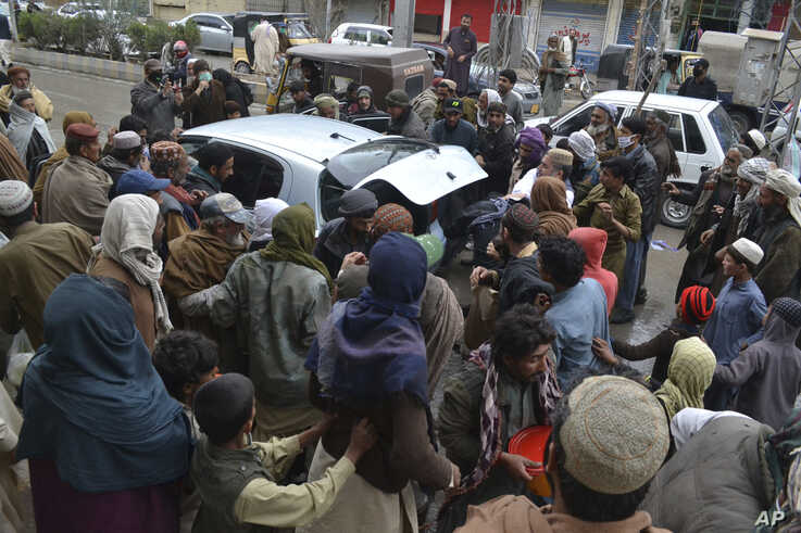 Daily wage workers, jobless due to coronavirus outbreak, rush to a car to receive free food distributed in Quetta, Pakistan,…