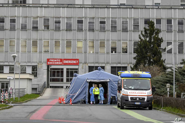 Paramedics stand by a tent that was set up outside the emergency ward of the Cremona hospital, northern Italy, Saturday, Feb…