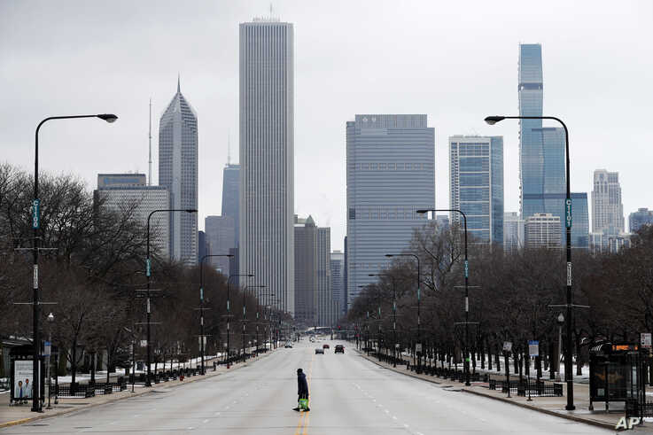 An elderly lady walks across the usually busy Columbus Drive that splits Chicago's Grant Park in half, on the first work day…