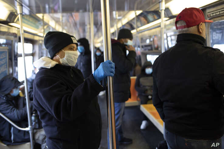 A subway rider wears a glove while holding a pole as several riders wear face masks during the coronavirus outbreak on the D…