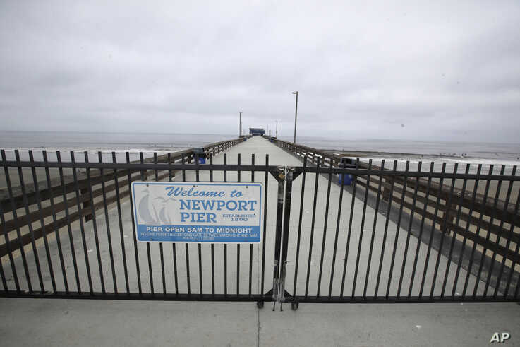 A pier is fenced off Thursday, April 30, 2020, in Newport Beach, Calif. A memo sent to California police chiefs says Gov. Gavin…