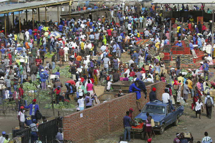 Hundreds of people buy goods at a fruit and vegetable market, despite a lockdown in an effort to curb the spread of the…