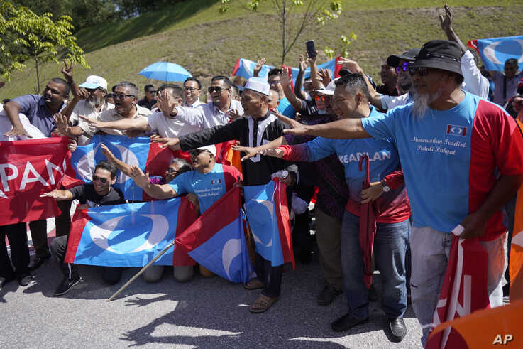 Supporters of People's Justice Party gather outside the National Palace to give support to Anwar Ibrahim in Kuala Lumpur,…