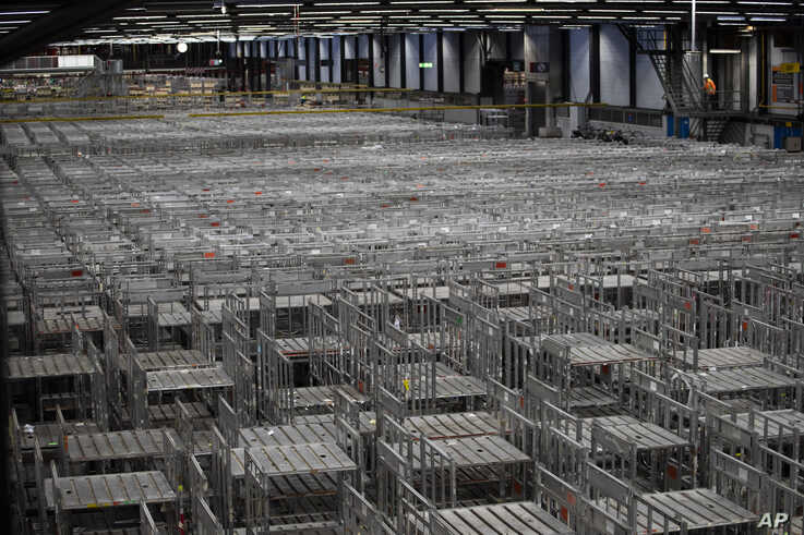 Empty racks are seen at flower auctioneer Royal FloraHolland in Aalsmeer, Netherlands, Thursday, March 19, 2020. Sales at major…