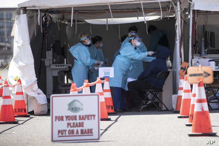 A medical worker administers a test for a COVID-19 at a facility in Camden, N.J., Wednesday, April 1, 2020. (AP Photo/Matt…