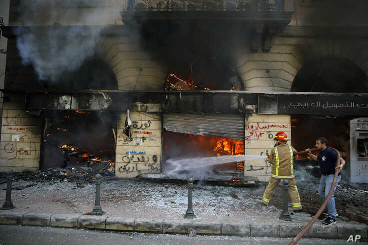Firefighters extinguish a fire at a branch of the Credit Libanais Bank that was burnt by anti-government protesters, in the…