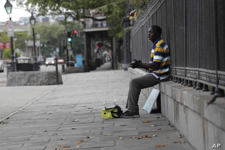 A street artist sings to no one along Jackson Square in the French Quarter of New Orleans, normally bustling with tourists, but…