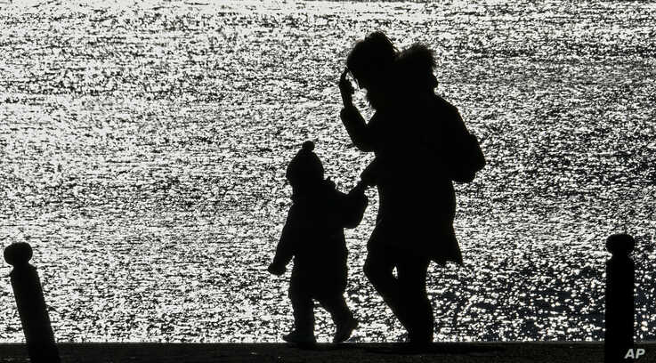 A mother and a child walk in the evening sun at a lake in Gelsenkirchen, Germany, Sunday, March 22, 2020. In order to slow down…