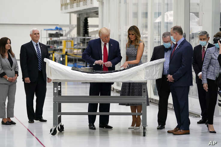 President Donald Trump looks at an area on a piece of equipment to sign during tour of NASA facilities before viewing the…