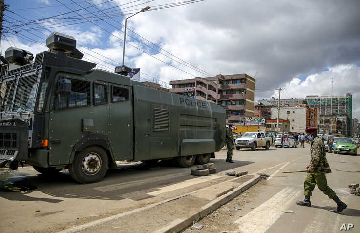 A police water cannon truck blocks a street to prevent residents from leaving the Eastleigh area of Nairobi, Thursday, May 7,…