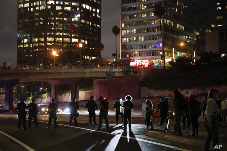 Protesters confront police officers while blocking the 110 Freeway during a protest over the death of George Floyd Friday, May…