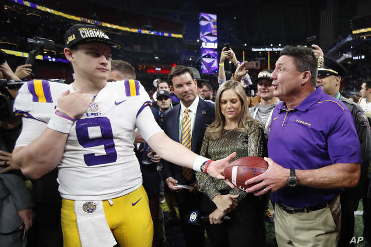 LSU quarterback Joe Burrow and LSU head coach Ed Orgeron celebrate after the Southeastern Conference championship NCAA college…