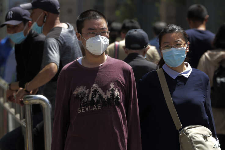 People wearing protective face masks to help curb the spread of the new coronavirus walk in downtown Beijing, Monday, May 18,…