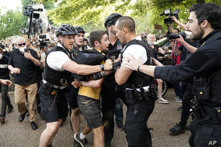 Uniformed U.S. Secret Service police detain a protester in Lafayette Park across from the White House as demonstrators protest…