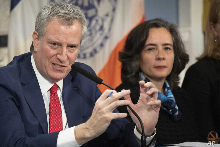 FILE - In this Wednesday, Feb. 26, 2020, file photo, Mayor Bill de Blasio, left, with Dr. Oxiris Barbot, commissioner of the…
