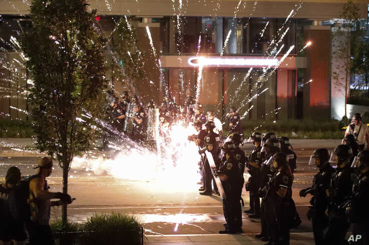 A firework explodes by a police line as demonstrators gather to protest the death of George Floyd, Saturday, May 30, 2020, near…
