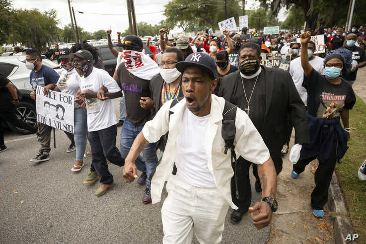 Malik Muhammad, center, joins a group of people marching from the Glynn County Courthouse in downtown to a police station after…