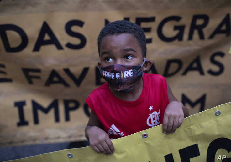 A black boy wearing a mask against the spread of the new coronavirus, holds a sign during a protest against racism and police…