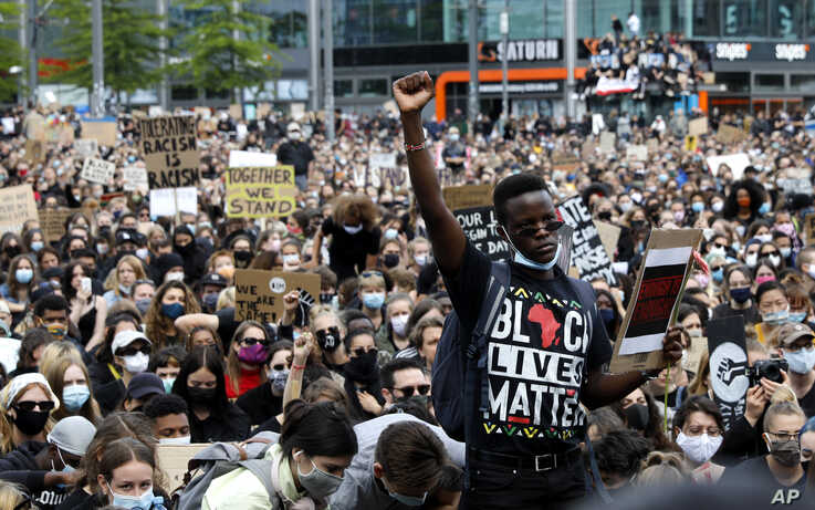 A man raises his fist as people gather in Berlin, Germany, Saturday, June 6, 2020, to protest against the recent killing of…