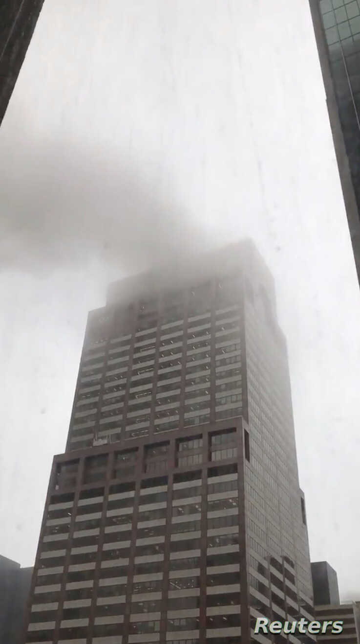 Smoke is seen rising from a building after a helicopter crash in New York City